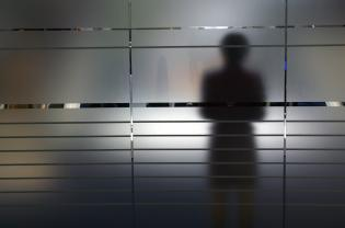 Shadow of a woman on a frosted glass pane, Symbolic photo to the topics: anonymity, fear, uncertainty, unsteadiness, personal secrets etc.