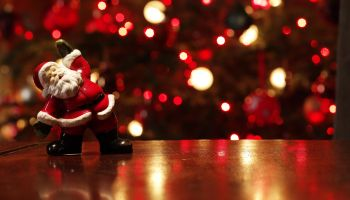 Santa figurine on table in front of Christmas tree