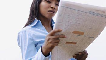 A businesswoman on a break reading a newspaper outdoors