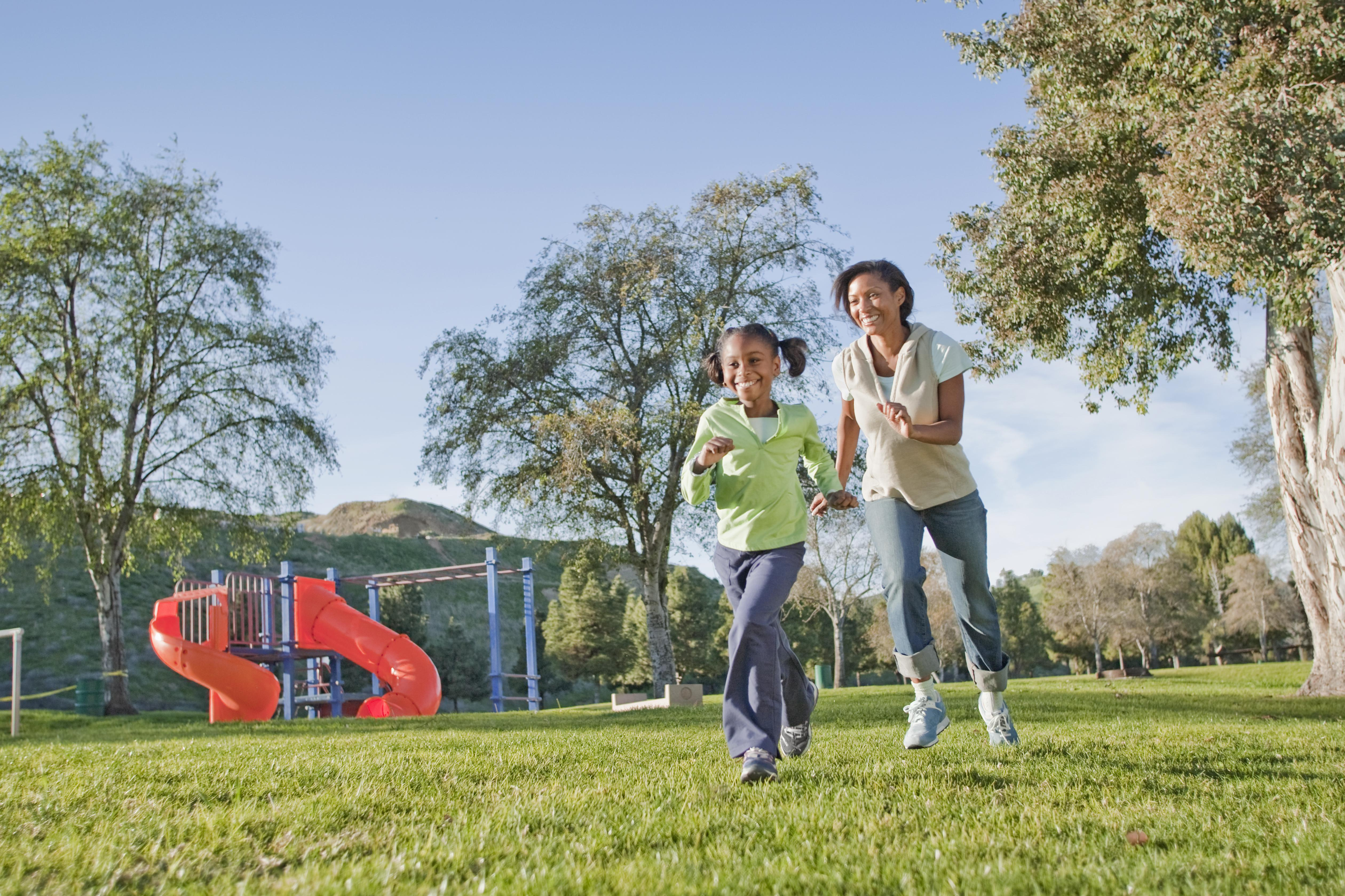 Mother and daughter running in a park