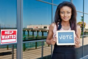 Young woman holding a sign that says 'VOTE'