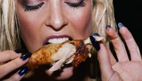 Young woman eating chicken leg, close up