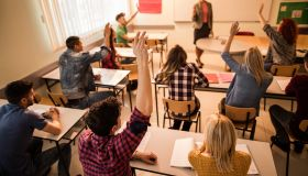 Students in the classroom raising hands to answer teacher's question.