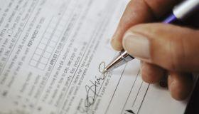 Man Signing Tax Form