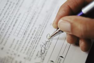 Man Signing Tax Form