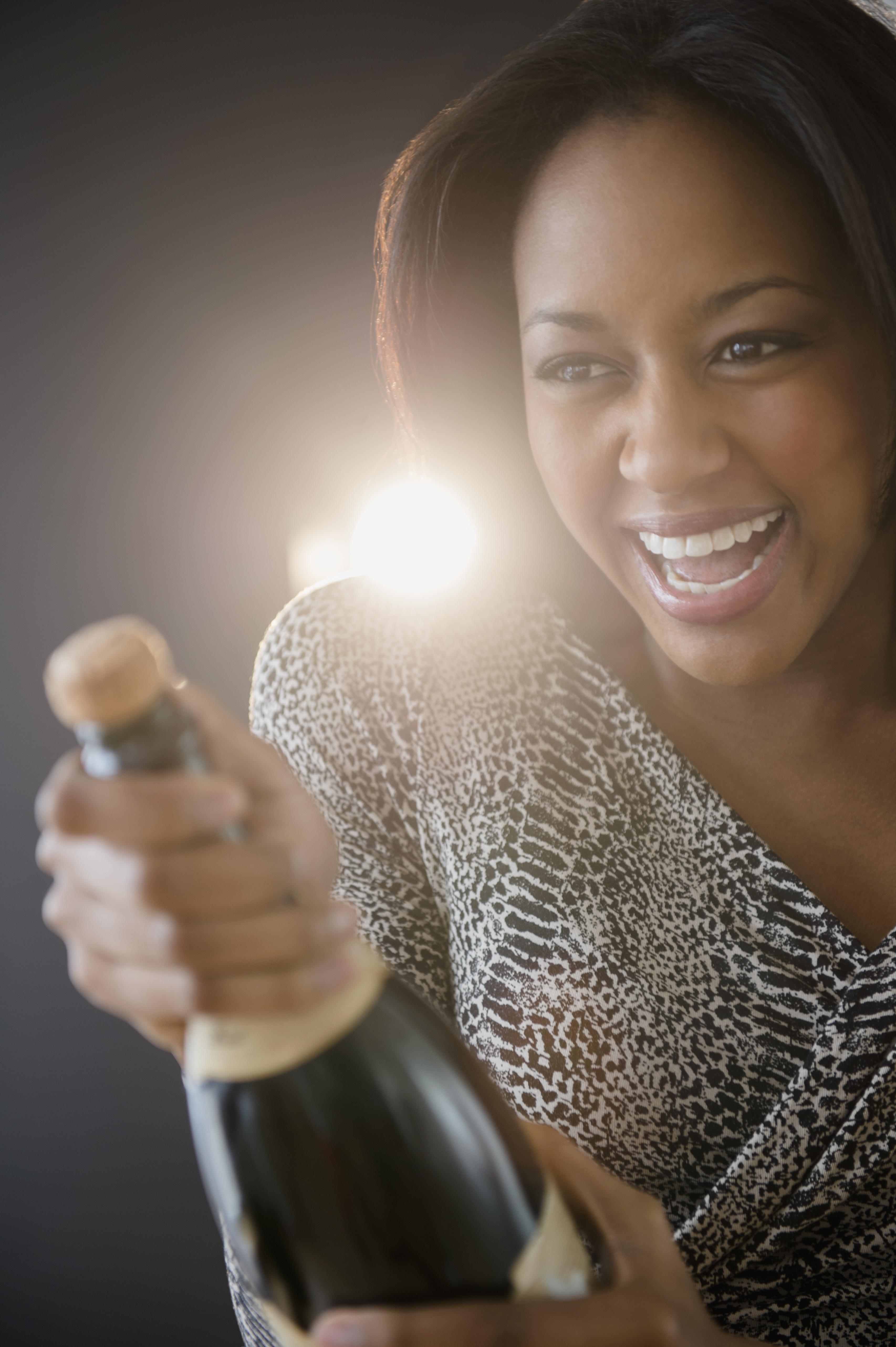 African American woman opening champagne bottle