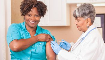 Doctor or nurse gives flu vaccine to patient at clinic.