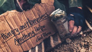 Fighting adversity. Homeless man sleeping with sign and money tin