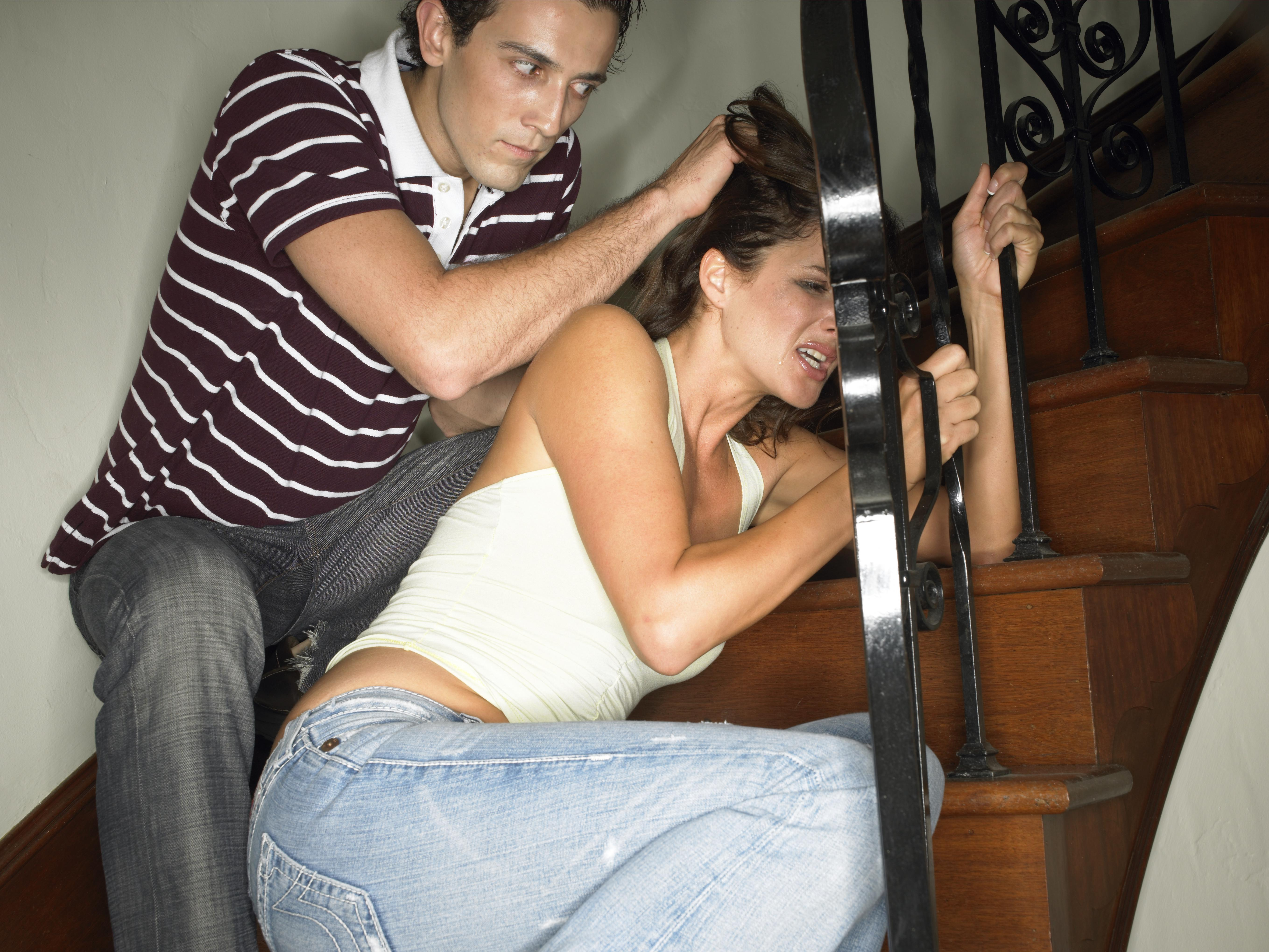 Young man pulling young woman by hair