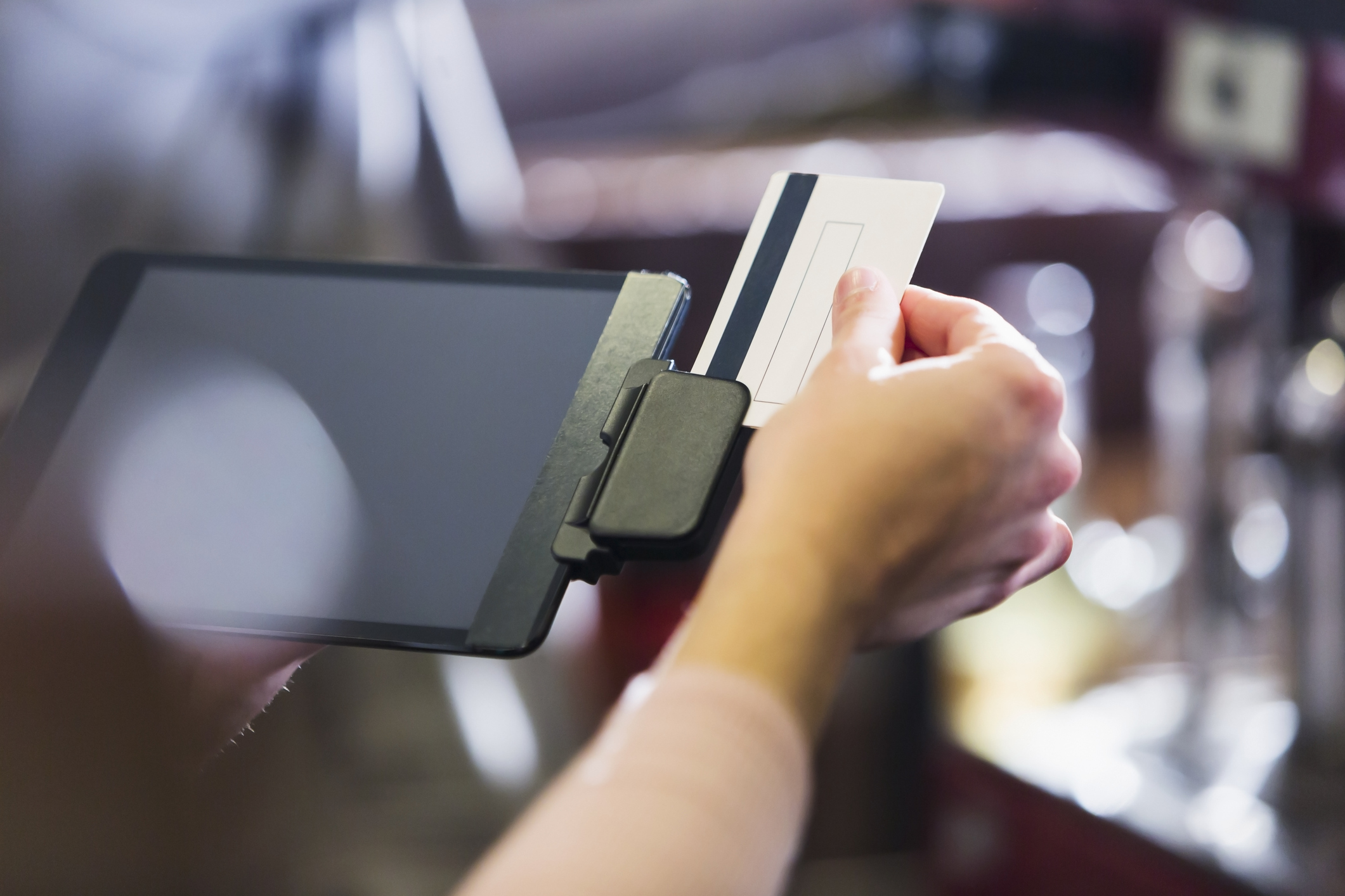 Hand of woman sliding credit card through reader