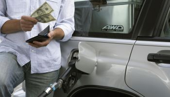 Man removing bank notes from wallet while refuelling car, mid section