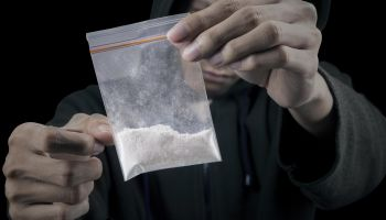 Drug dealer is preparing packet of heroin or cocaine