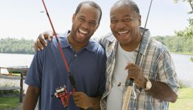 Portrait of father and son with fishing poles