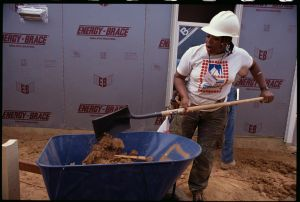 Habitat for Humanity Worker Shovels Dirt Into Wheelbarrow