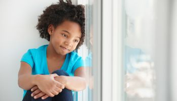 Black girl sitting in windowsill