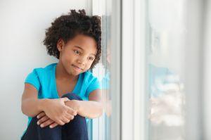Black girl sitting in windowsill