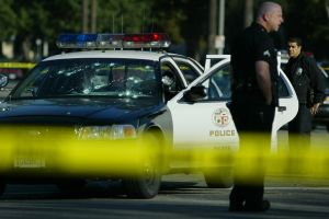 A bullet–riddled LAPD patrol car sits disabled on St. Andrews Place and Venice Blvd Thursday morning