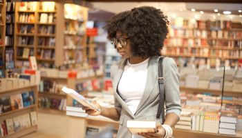 Woman with afro hair choosing books in a bookstore