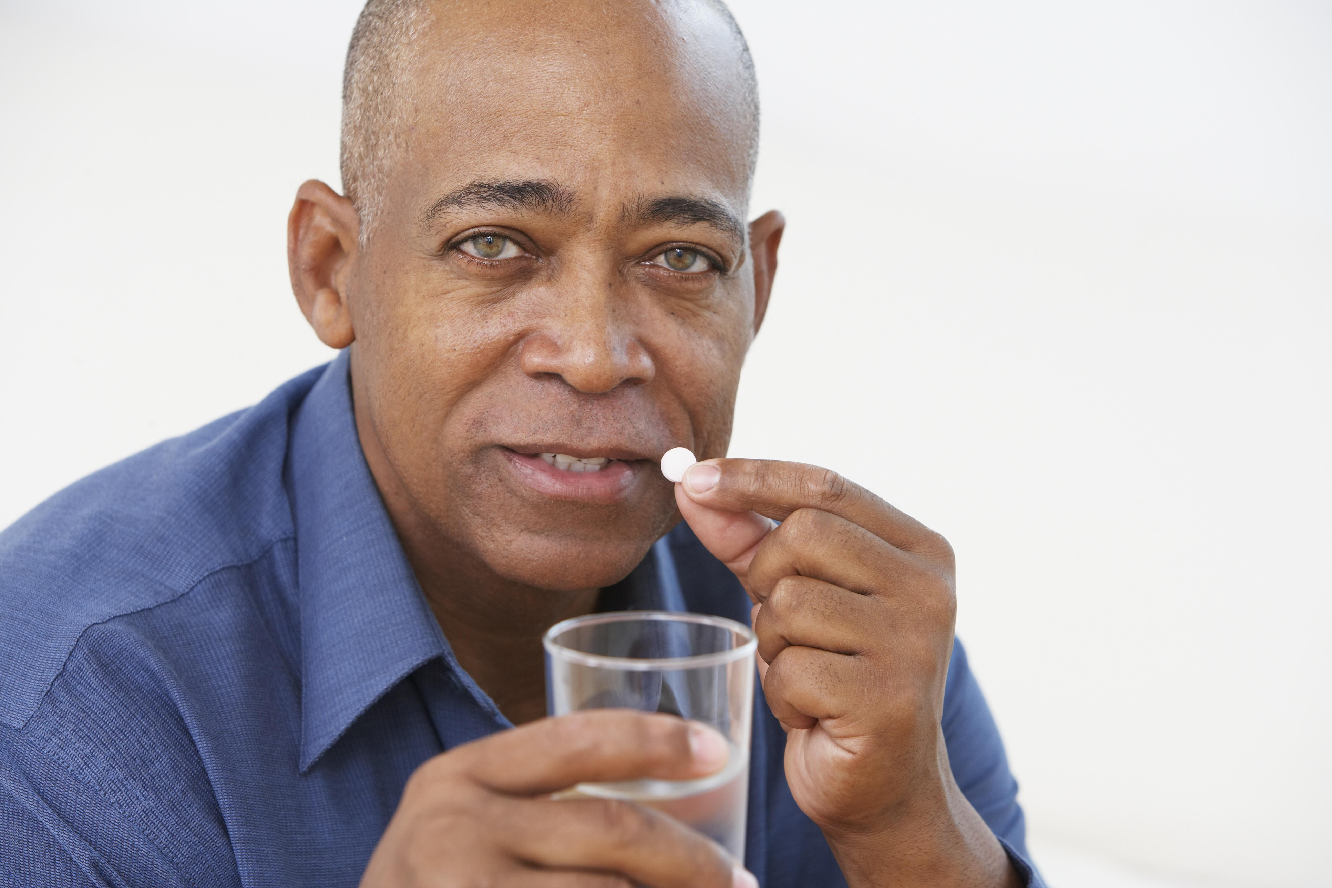 Senior African man taking medication with glass of water