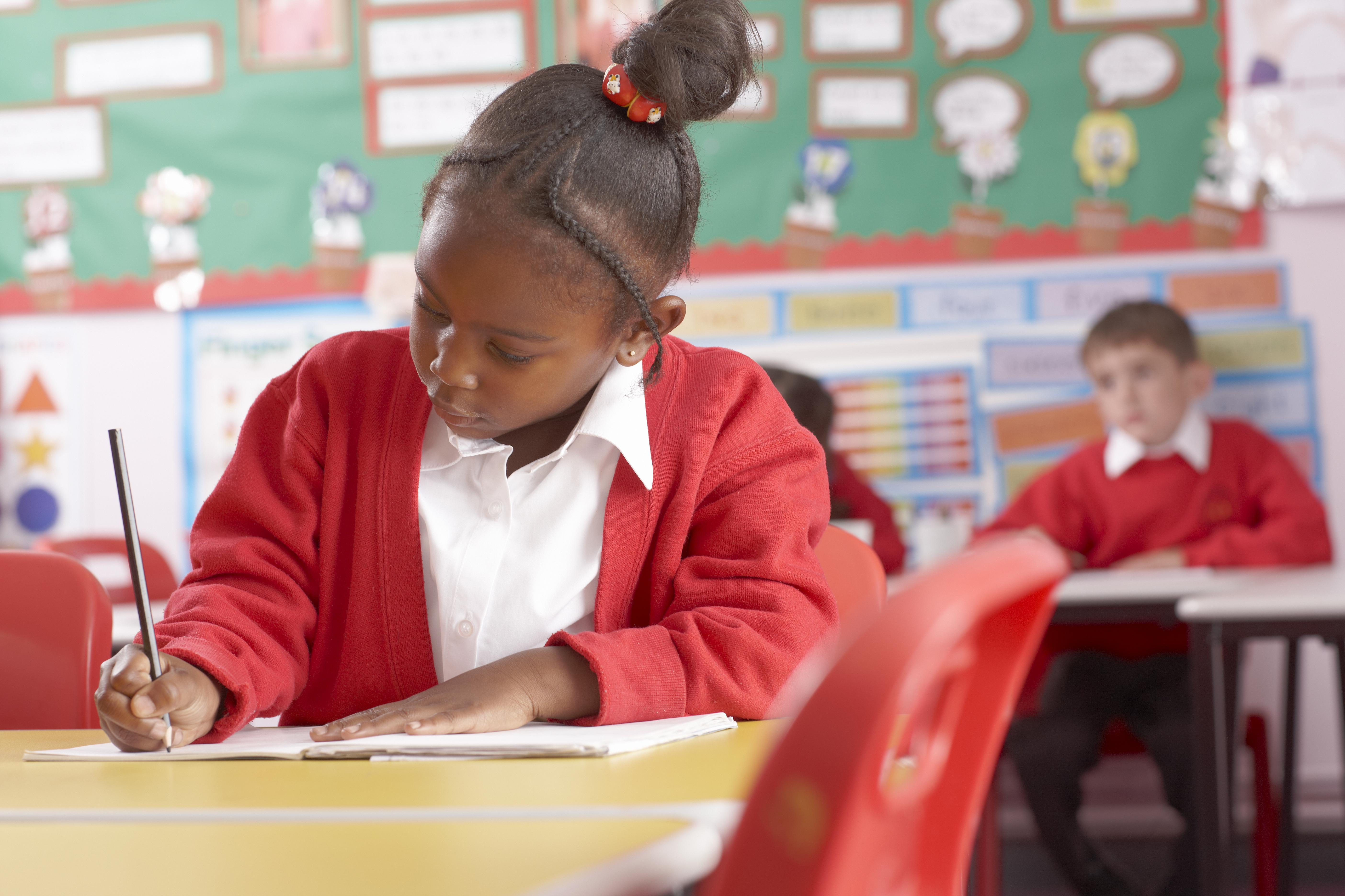 School child writing in book