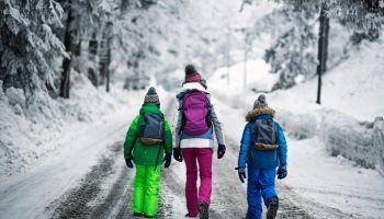 Kids with backpacks walking on winter road