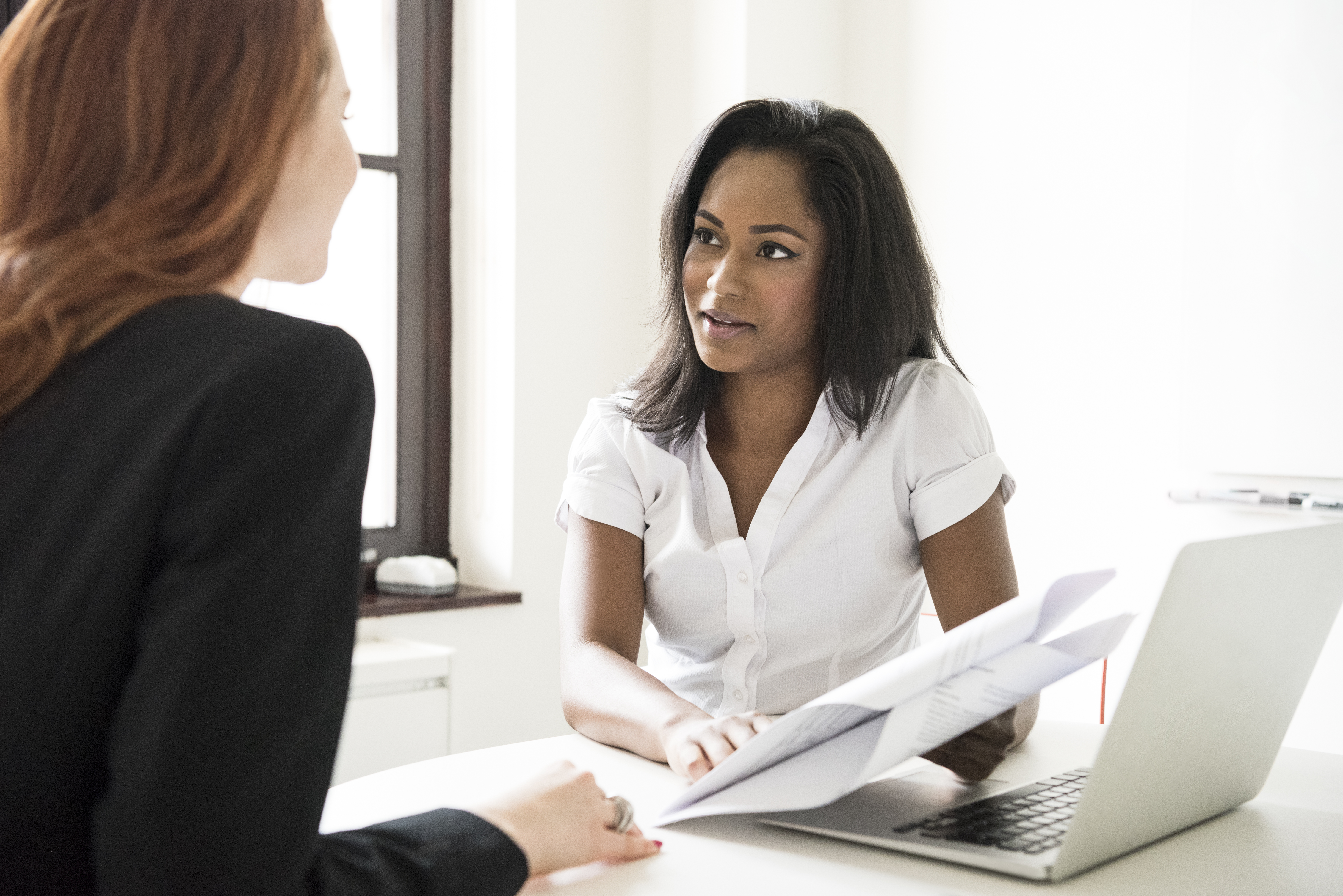Young businesswoman with documents and laptop talking to colleague