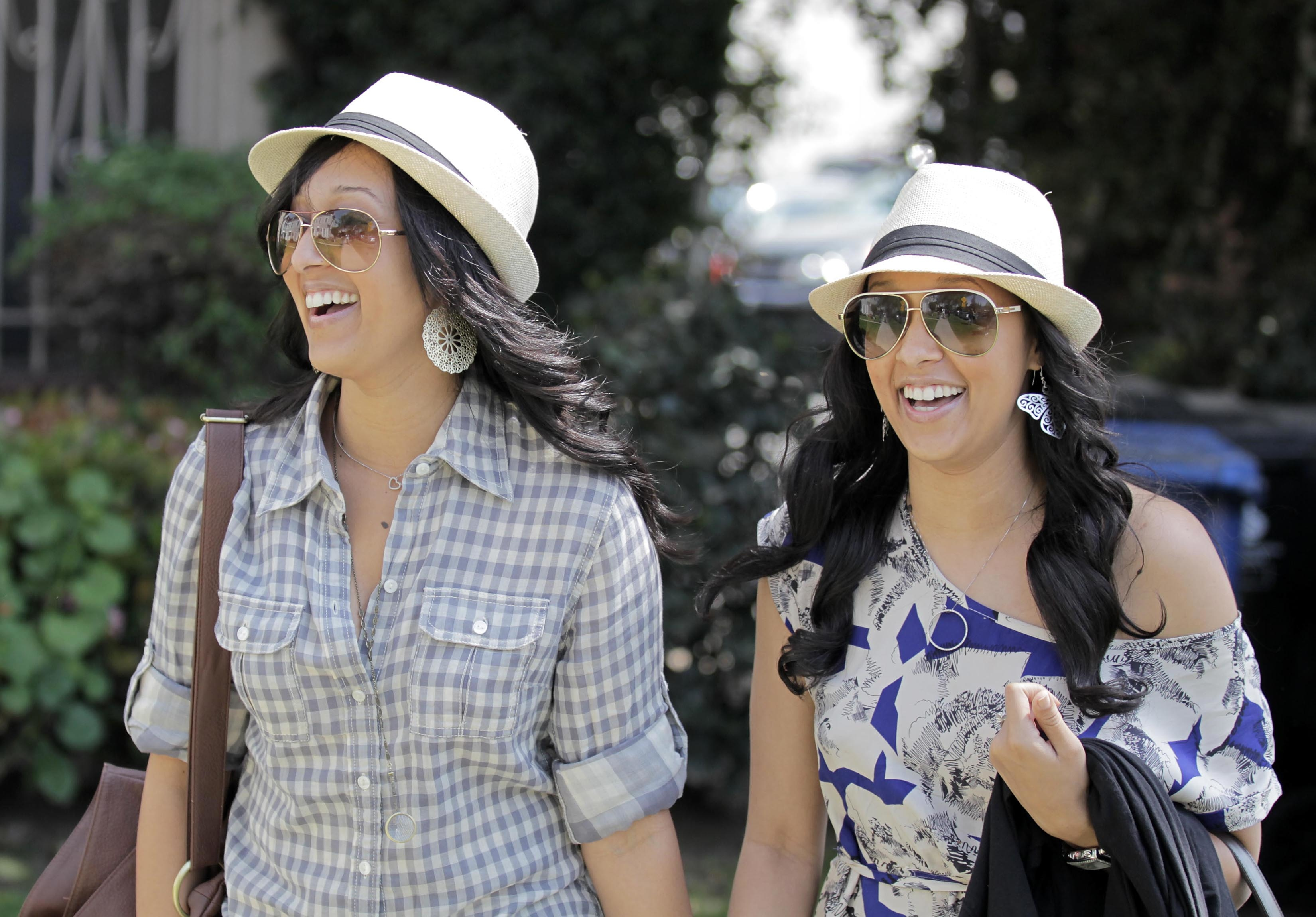 TIA AND TAMERA MOWRY SMILING AND HOLDING HANDS