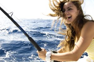 Portrait of a young woman fishing and smiling