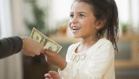 Mother handing girl one dollar bill