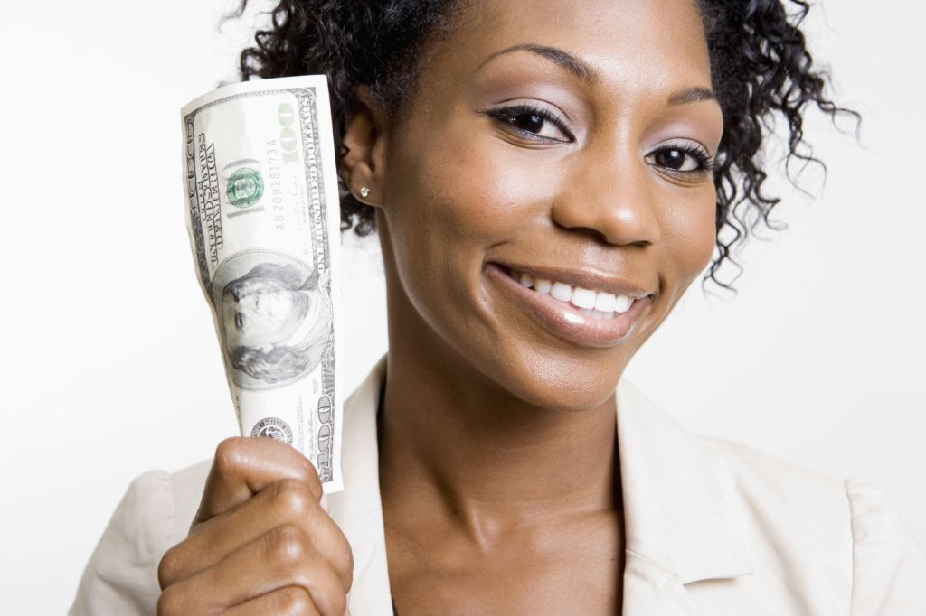 African American woman holding hundred dollar bill