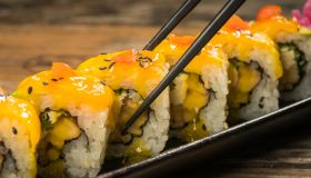 Yellow sushi roll with chopstick on the plate.