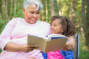 Grandmother and grandchild reading books outdoors together.