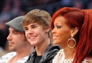 Singers Justin Bieber (C) and Rihanna (R