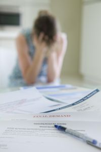 woman head in hands with a stack of unpaid bills