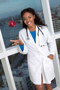 African American female doctor tossing apple