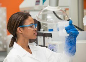 Black scientist examining liquid in laboratory