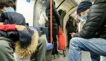 People wearing masks travel on the Victoria Line of the London Underground, London on Friday, Mar. 20, 2020 .
