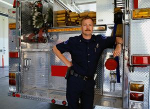 Firefighter leaning against rear of fire engine, portrait