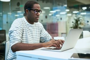 African Young Man Using Laptop in Office