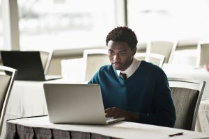 Mixed race businessman using laptop in convention room