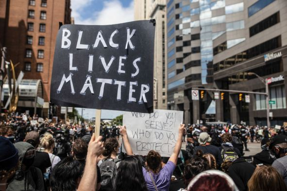 A protester holds a placard that says Black Lives Matter...