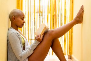 Latin woman reads a book in one of the hallways of the house
