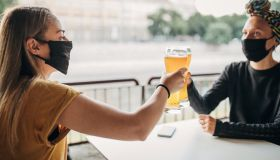 Two women with black face masks drinking beer in cafe outdoors
