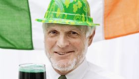 Elderly man dressed as a leprechaun holding a glass of stout
