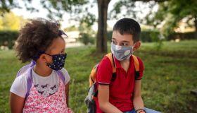 School kids in schoolyard wearing face protective mask